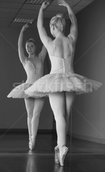 Graceful ballerina standing en pointe in front of mirror Stock photo © wavebreak_media