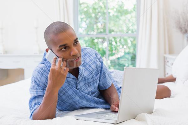 Gelukkig man met behulp van laptop bed praten telefoon Stockfoto © wavebreak_media