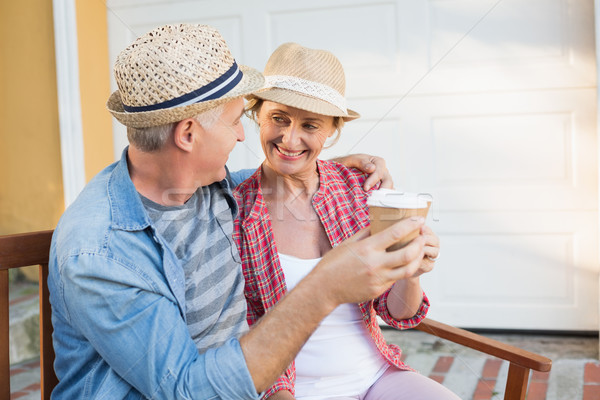 Happy mature couple drinking coffee on a bench in the city Stock photo © wavebreak_media