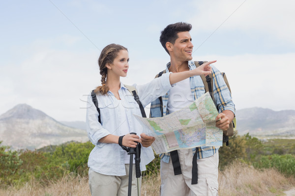 Hiking couple with map pointing ahead on mountain terrain Stock photo © wavebreak_media