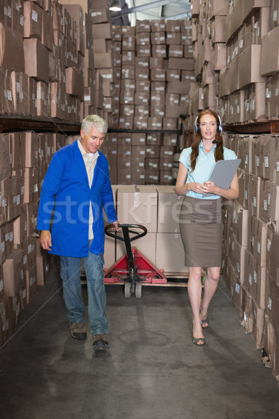 Warehouse manager walking with foreman pulling trolley Stock photo © wavebreak_media