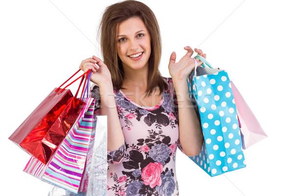 Mosolyog fiatal nő tart bevásárlótáskák fehér portré Stock fotó © wavebreak_media
