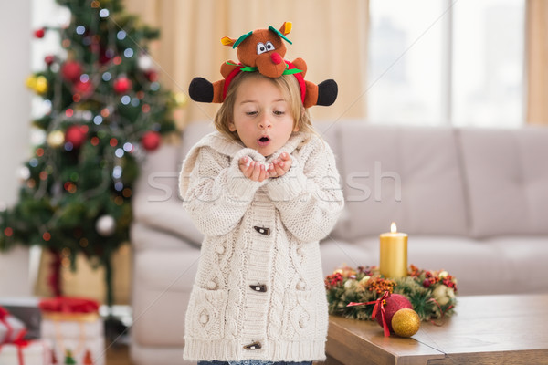 Festive little girl blowing over hands Stock photo © wavebreak_media