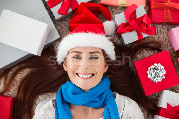 Festive redhead smiling at camera with gifts Stock photo © wavebreak_media