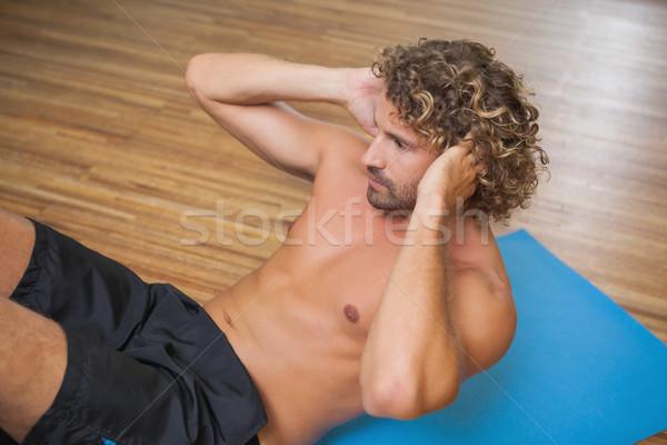 Shirtless young man doing push ups in gym Stock photo © wavebreak_media