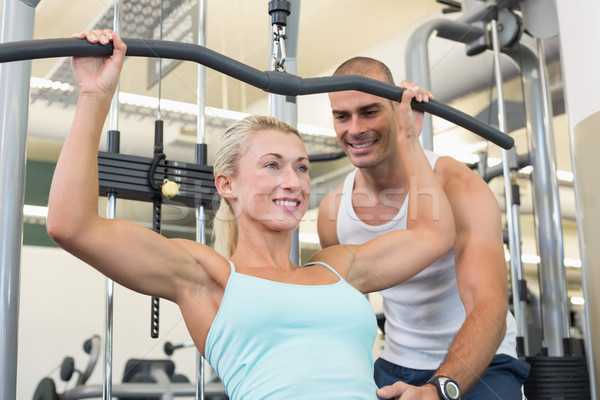 Male trainer assisting woman on a lat machine in gym Stock photo © wavebreak_media