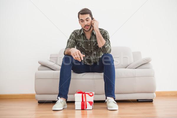 Confusi uomo guardando regali piano home Foto d'archivio © wavebreak_media
