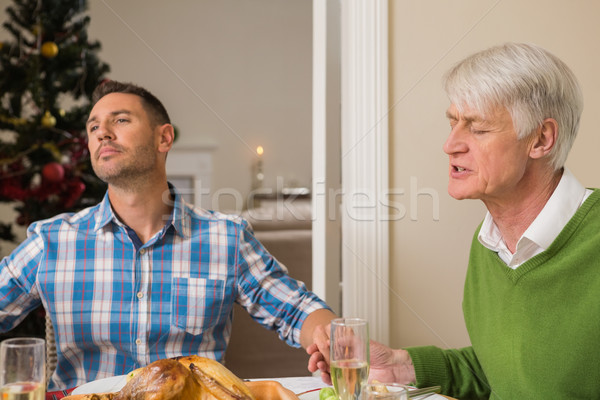Extended family saying grace before christmas dinner Stock photo © wavebreak_media