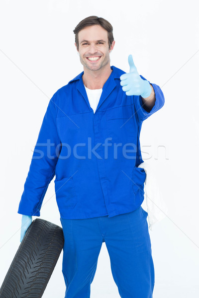 Mechanic holding tire while showing thumbs up Stock photo © wavebreak_media