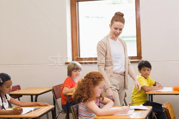 Stock photo: Pretty teacher helping pupils in classroom