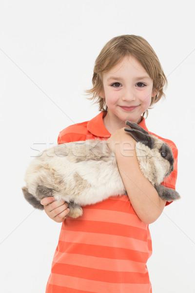 Cute boy holding bunny on white background Stock photo © wavebreak_media