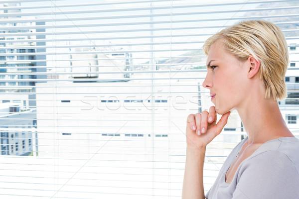 Thoughtful woman standing by the window Stock photo © wavebreak_media