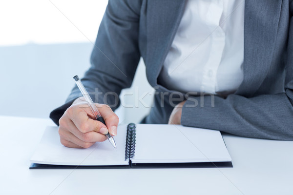 Femme d'affaires écrit journal bureau femme costume Photo stock © wavebreak_media