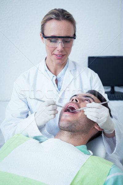Female dentist examining mans teeth Stock photo © wavebreak_media