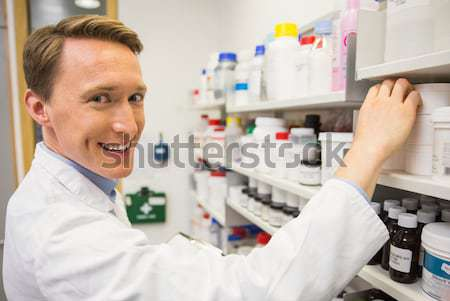 Junior pharmacist taking medicine from shelf Stock photo © wavebreak_media