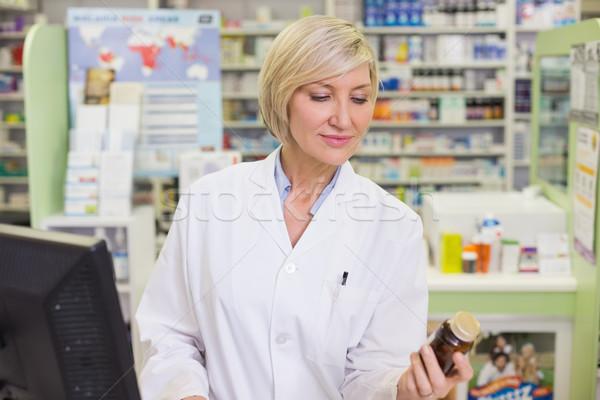 Pharmacist looking at medicine bottle  Stock photo © wavebreak_media