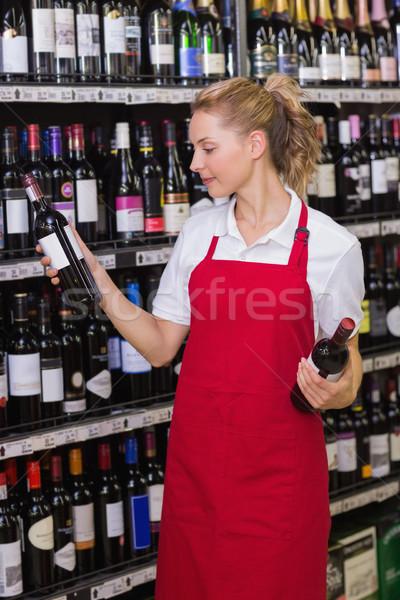 Glimlachend blond werknemer naar wijnfles supermarkt Stockfoto © wavebreak_media