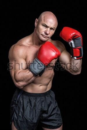 Composite image of boxer punching against black background Stock photo © wavebreak_media