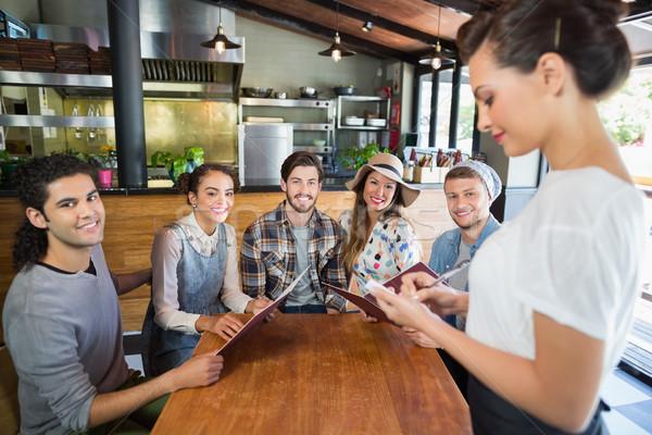 Amigos sesión camarera toma restaurante retrato Foto stock © wavebreak_media