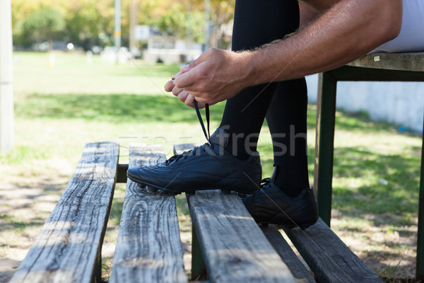 Low section of rugby player tying shoes on bench Stock photo © wavebreak_media