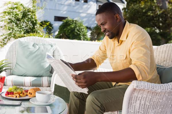 Moço leitura jornal sessão café café da manhã Foto stock © wavebreak_media