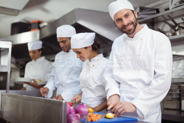 Chefs chopping vegetables on chopping board in the commercial kitchen Stock photo © wavebreak_media