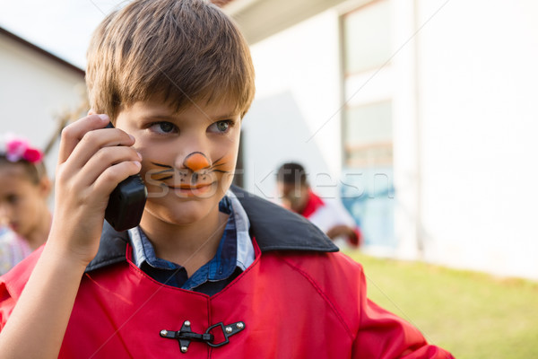 Boy with face paint using walkie talkie while looking away Stock photo © wavebreak_media