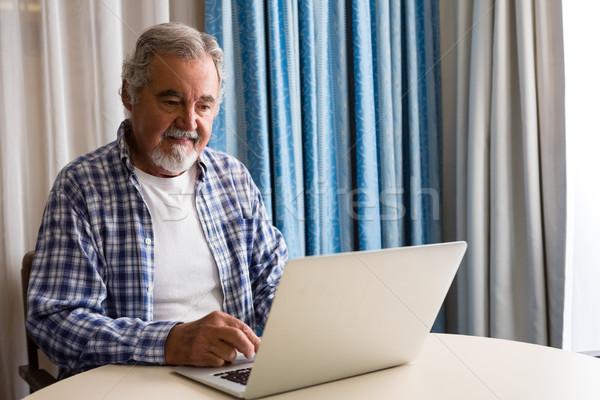 Senior homem usando laptop sessão tabela casa de repouso Foto stock © wavebreak_media