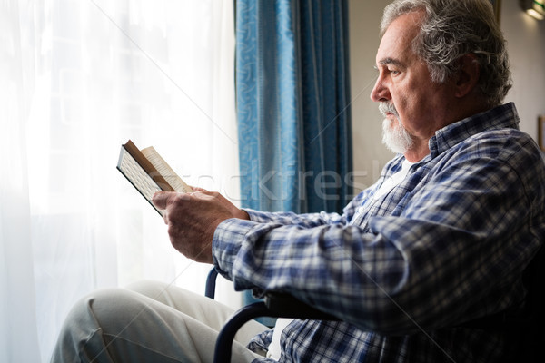 senior man reading book while sitting on wheelchair in nursing home Stock photo © wavebreak_media