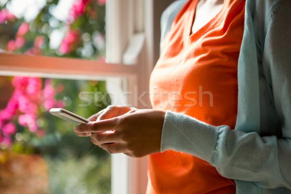 Középső rész nő okostelefon ablak otthon narancs Stock fotó © wavebreak_media