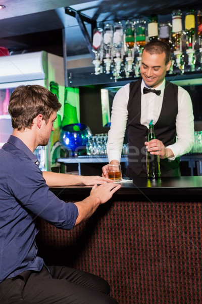 Bartender serving whiskey to man Stock photo © wavebreak_media