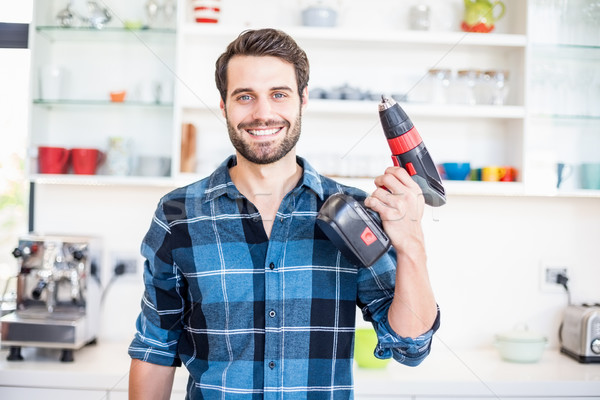 Portrait of happy man holding with drill machine in kitchen Stock photo © wavebreak_media
