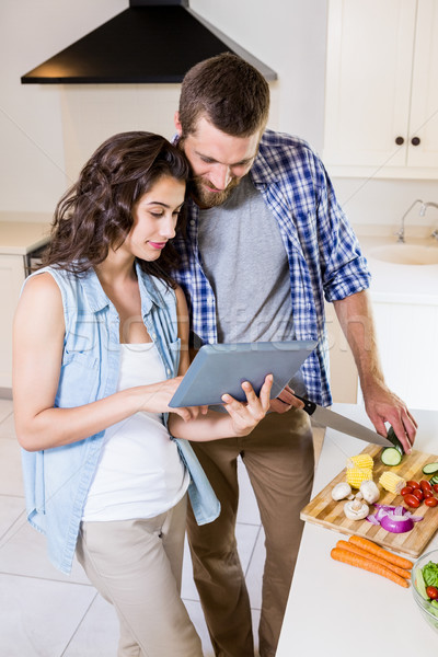 Woman using digital tablet and man chopping vegetables  Stock photo © wavebreak_media