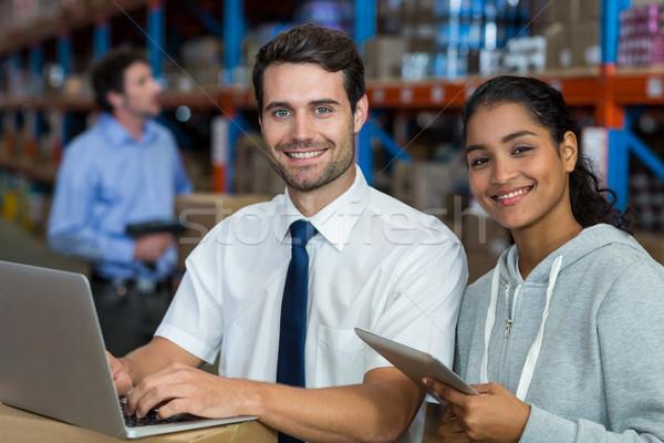 улыбаясь работник набрав компьютер склад бизнеса Сток-фото © wavebreak_media