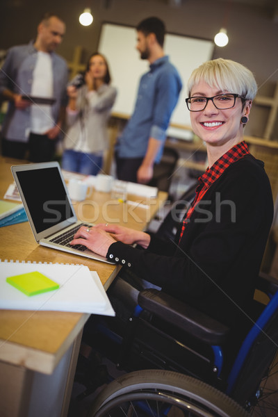 Smiling disabled businesswoman using laptop at desk  Stock photo © wavebreak_media