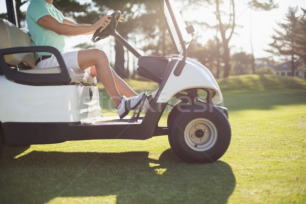 Low section of golfer man driving golf buggy Stock photo © wavebreak_media