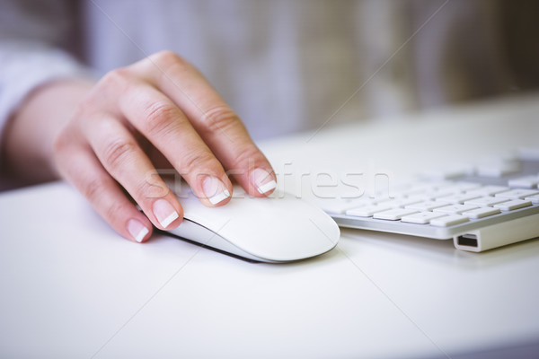 Cropped image of businesswoman using mouse on desk at office Stock photo © wavebreak_media