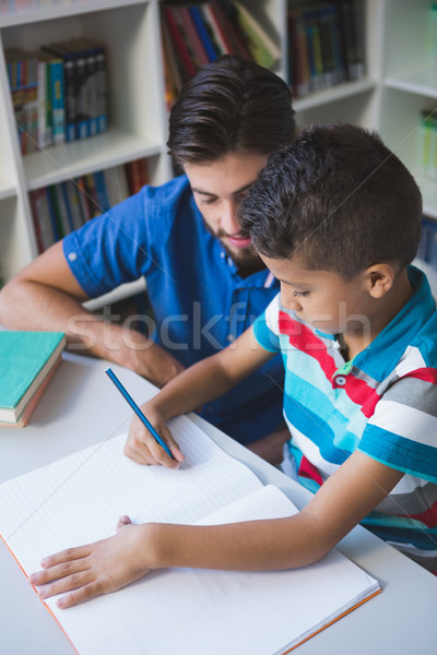 Teacher helping school kid with his homework in library Stock photo © wavebreak_media