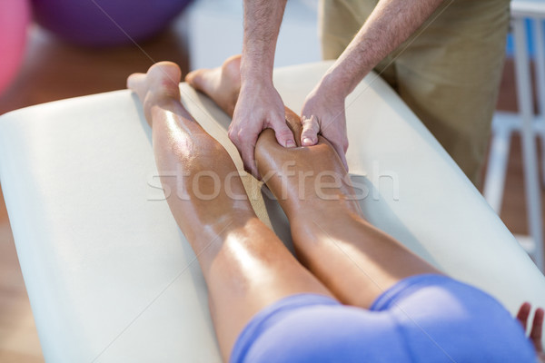 Male physiotherapist giving knee massage to female patient Stock photo © wavebreak_media