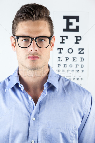Man wearing spectacles with eye chart in background Stock photo © wavebreak_media