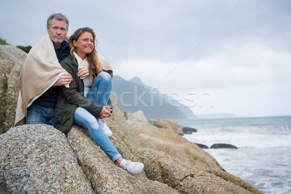 Casal sessão rochas praia homem feliz Foto stock © wavebreak_media