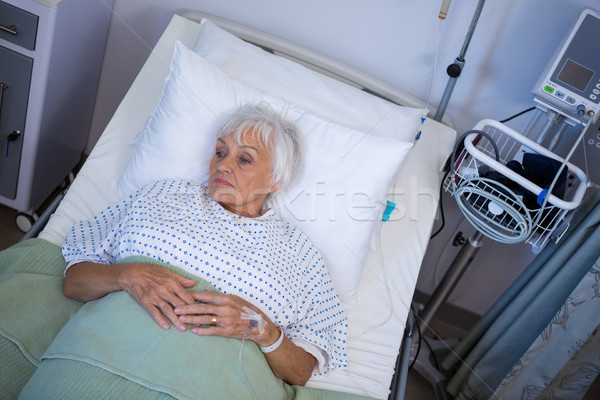 Thoughtful senior patient lying on bed Stock photo © wavebreak_media