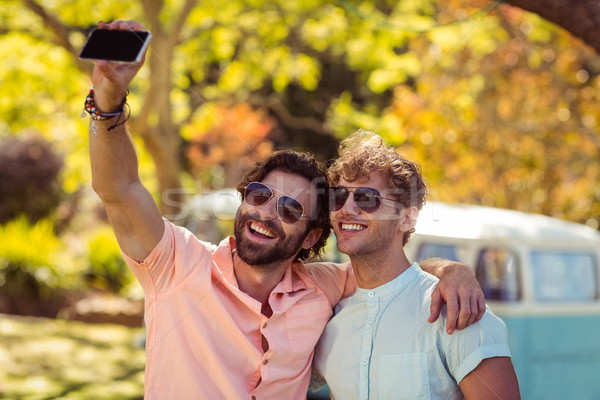 Two male friends taking selfie with mobile phone Stock photo © wavebreak_media