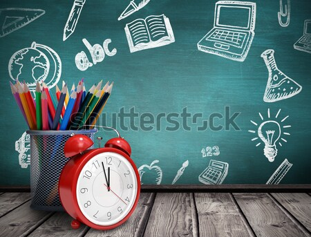 Books with alarm clock by colored pencils in mug on table against green Stock photo © wavebreak_media