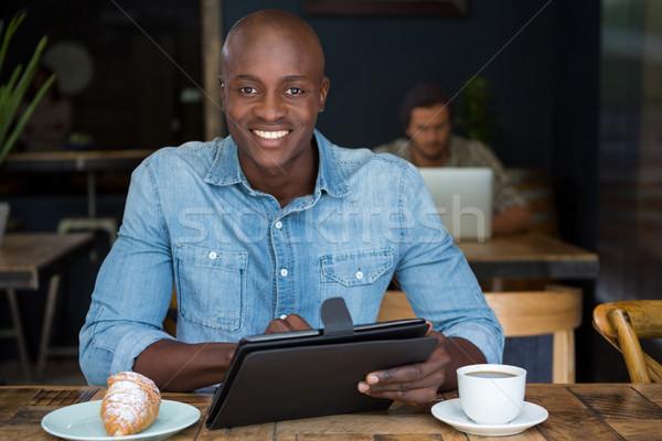 Boldog fiatalember táblagép asztal kávéház technológia Stock fotó © wavebreak_media