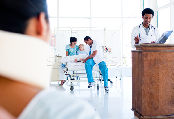Injured woman sitting on wheelchair and a medical team at work Stock photo © wavebreak_media