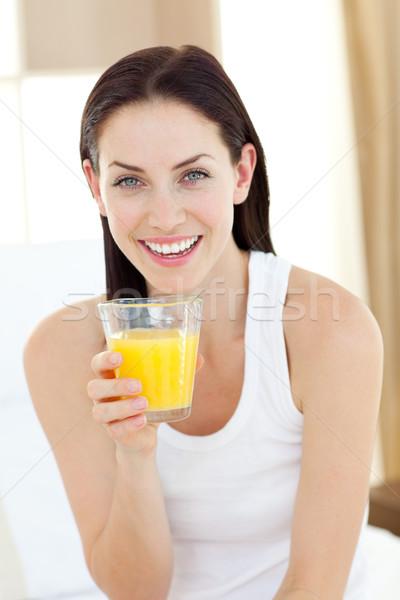 Smiling woman drinking orange juice sitting on her bed Stock photo © wavebreak_media