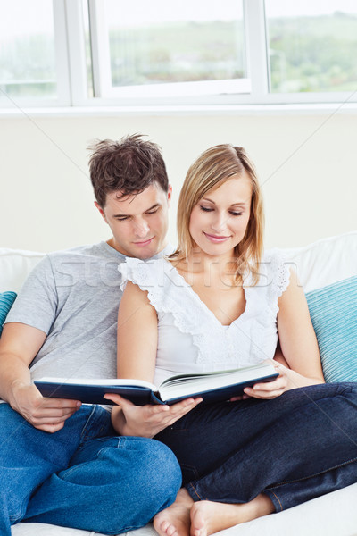 smart couple reading a book together sitting on the sofa in the living-room Stock photo © wavebreak_media