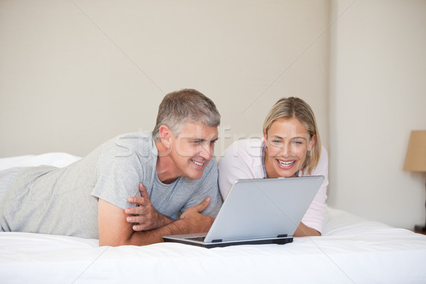 Lovely couple looking at their laptop at home Stock photo © wavebreak_media