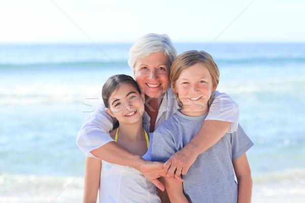 Stock fotó: Nagymama · unokák · tengerpart · égbolt · víz · mosoly